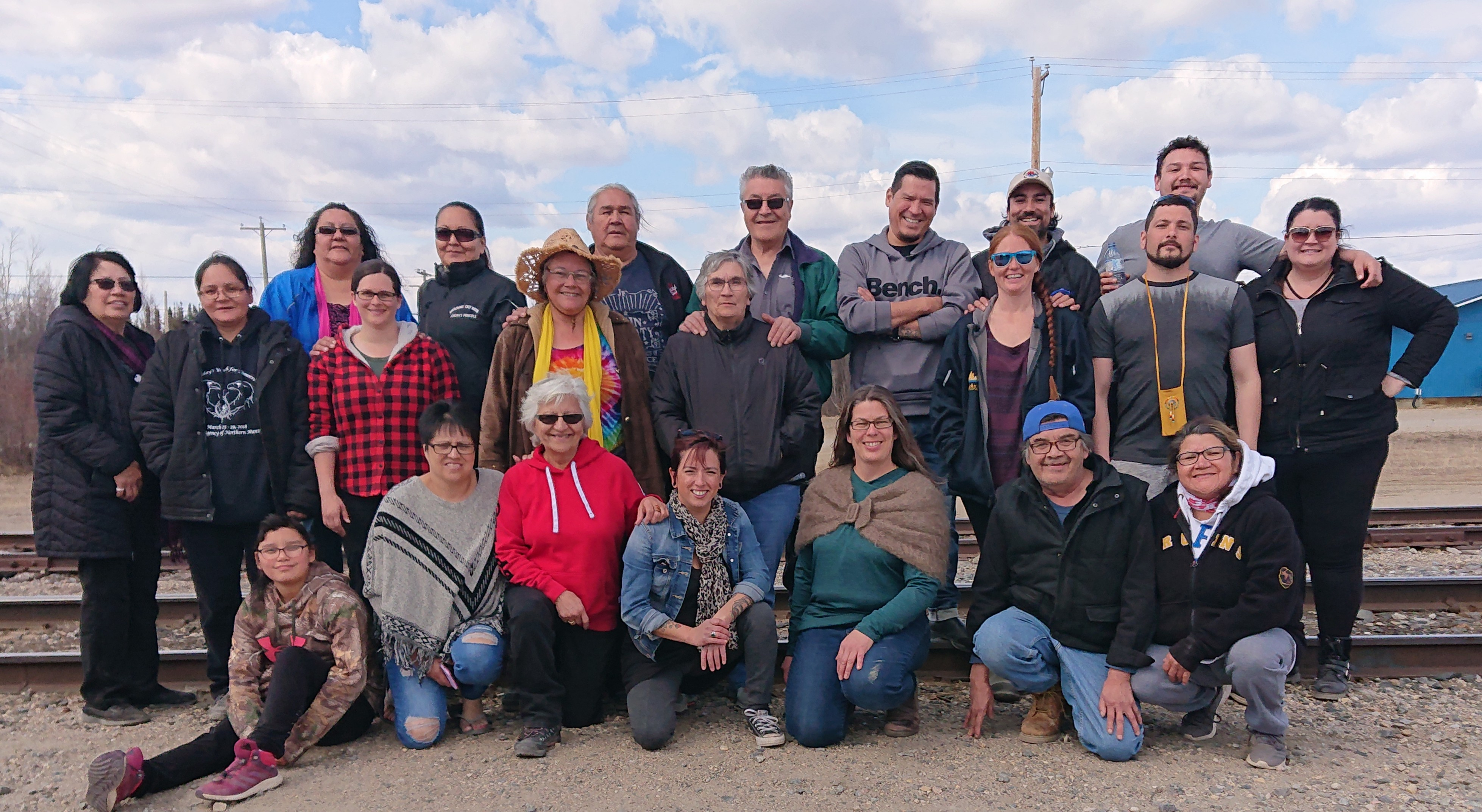 Group of NMFCCC members, standing outside in three rows, who work to support sustainable food solutions in the Northern Manitoba region.
