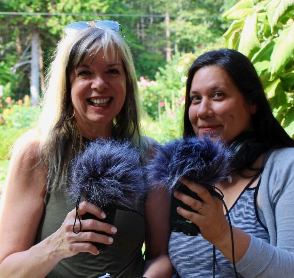 Two women holding up microphones with fuzzy windscreen to record for podcast workshop.