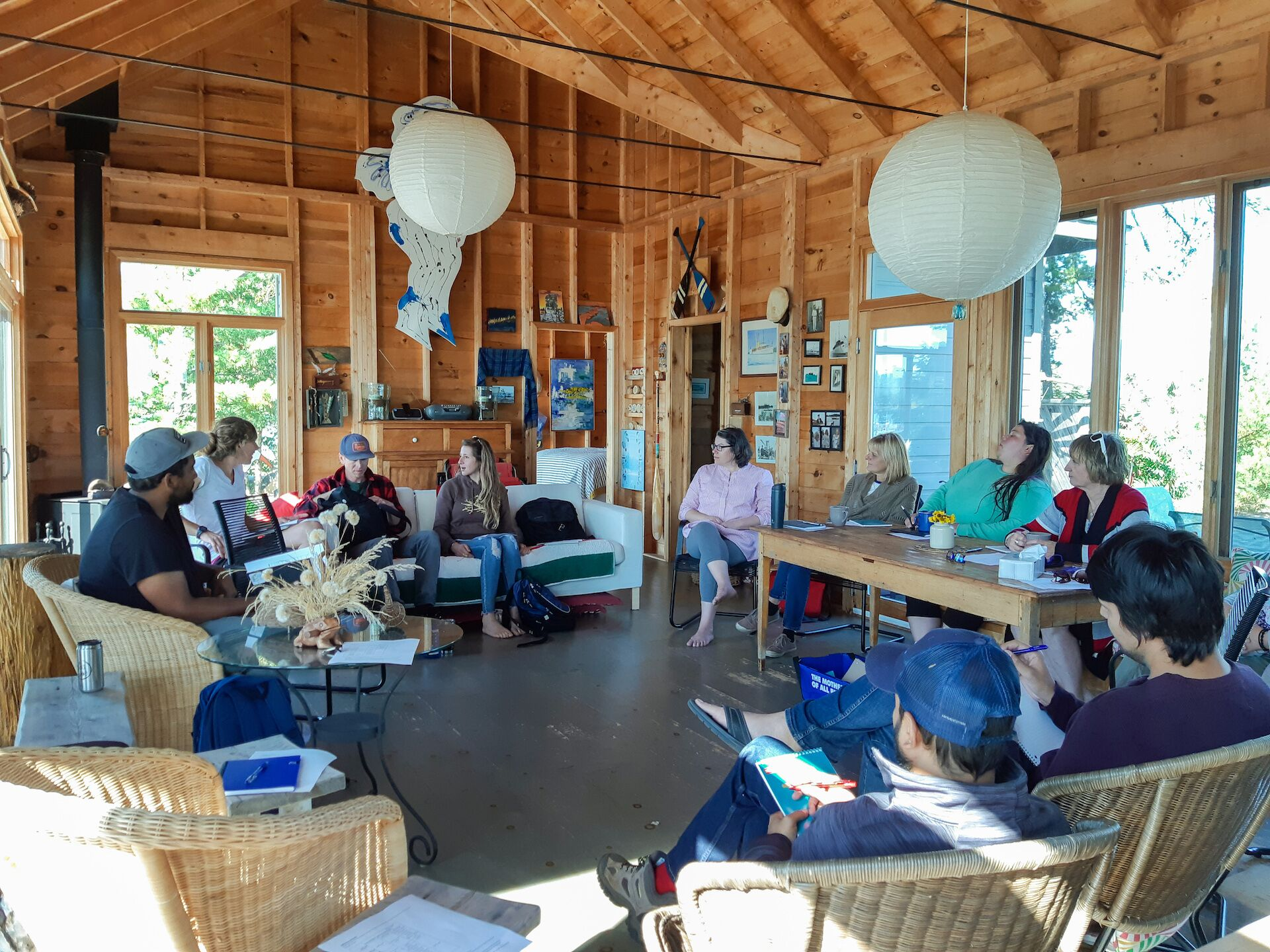 A group of people sitting in a circle in a cabin for a group discussion at staff retreat funded by Dragonfly Fund Emotional Health and Well-Being grant program.