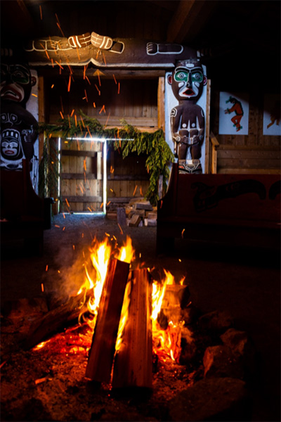 Warmth of the fire welcomes all inside the Big House Gwa Yas Dums Village, Gilford Island