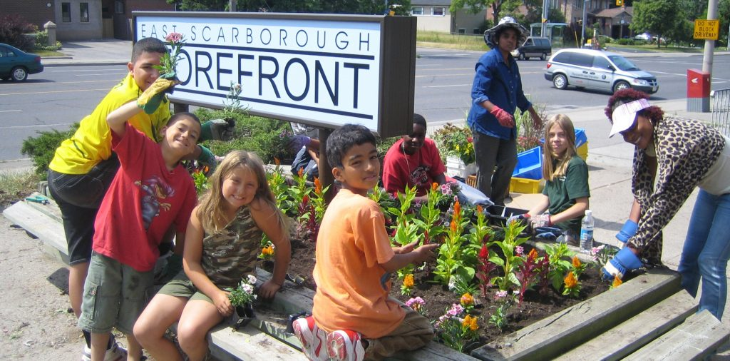 Children and adults planting outside The Storefront.