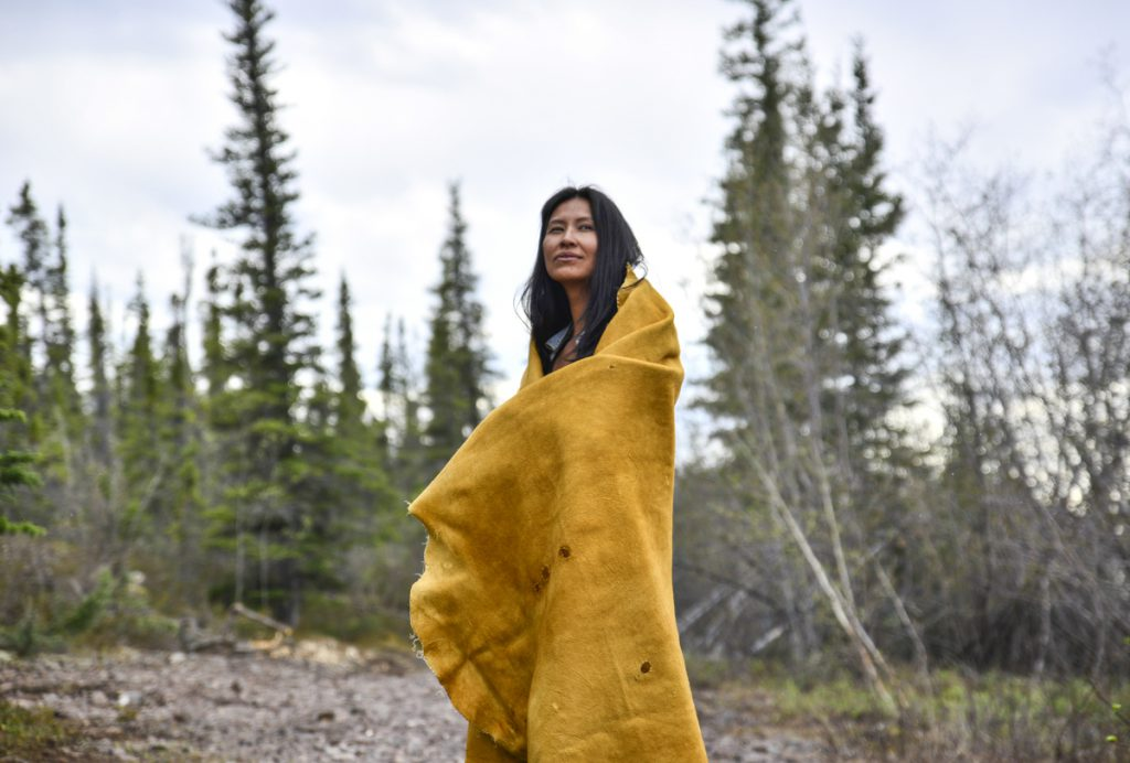 woman wrapped in blanket in forest