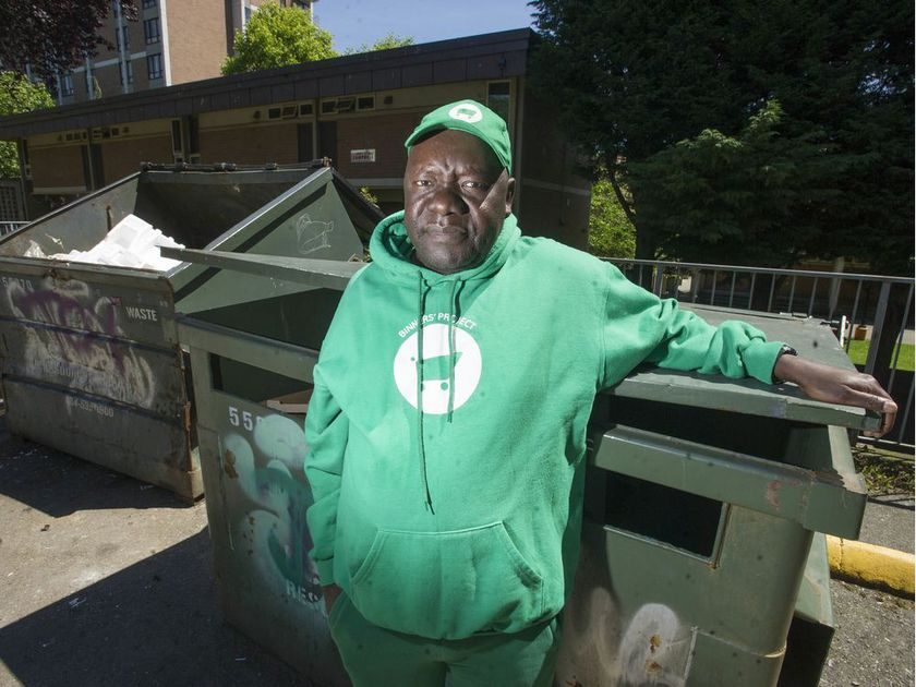 man stands in front of dumpster wearing green sweater