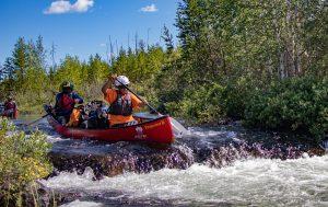 Two boys canoe through a river rapid