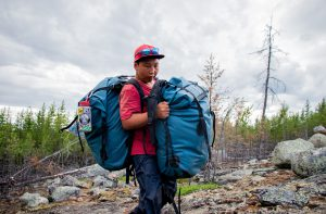 Boy carries two backpacks while portaging on a canoe trip