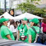women in green shirts stand in circle at street market