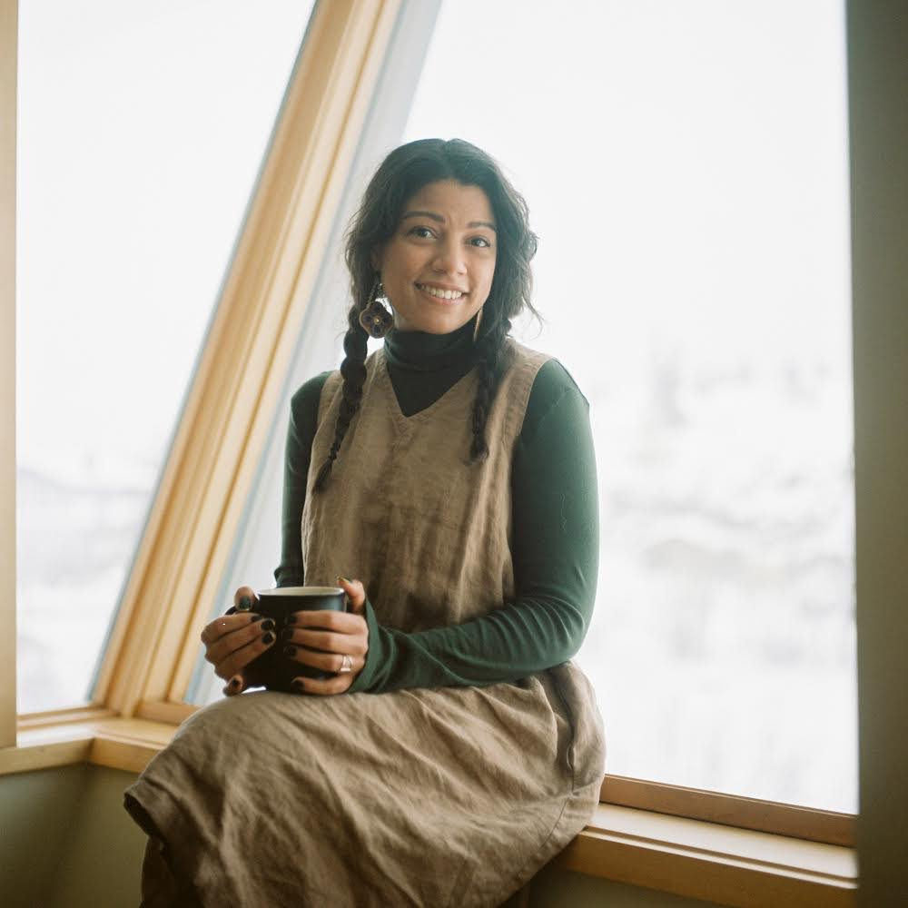 Sabrina sits in a windowsill with a cup of tea
