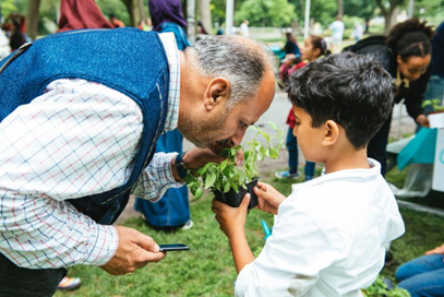 A boy holds up herbs for a man to smell