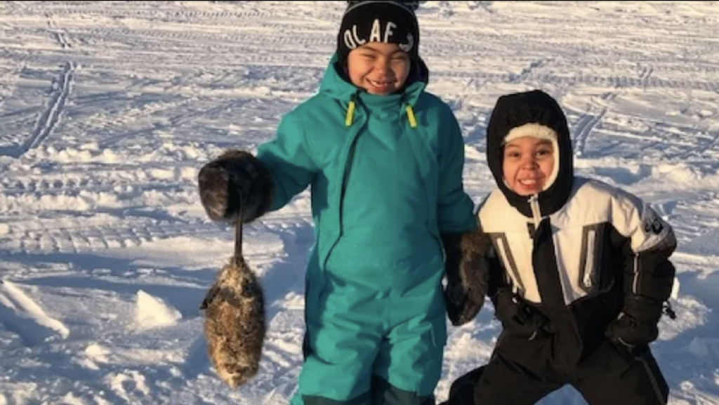 Two boys trap muskrats in the North