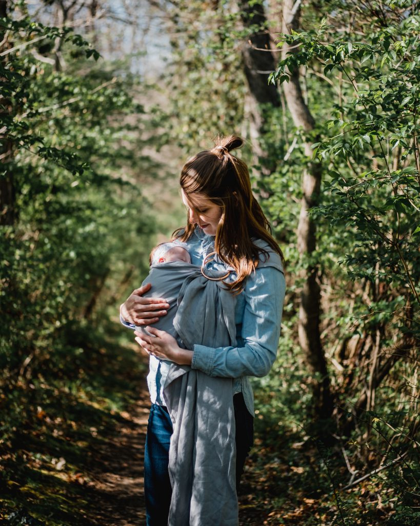 A woman stands with her baby in a grove of trees.