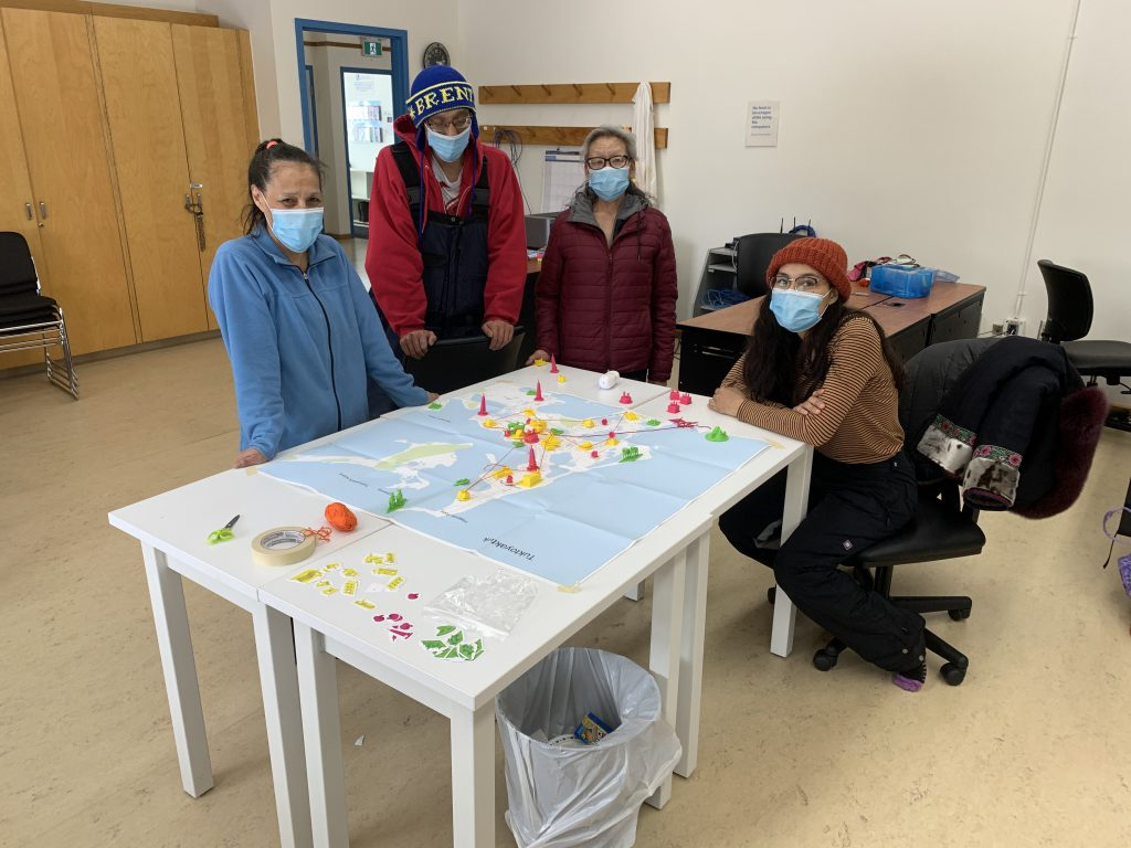 A group of people wearing masks sit around a table with a map.