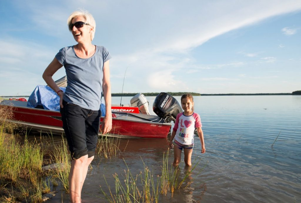 Pegi stands near a boat and a small girl on a lake in the Northern Territories
