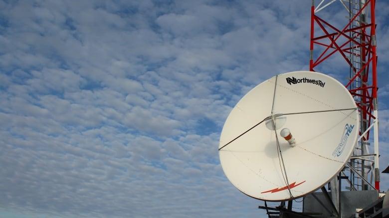A Northwestel satellite dish against a blue sky background.