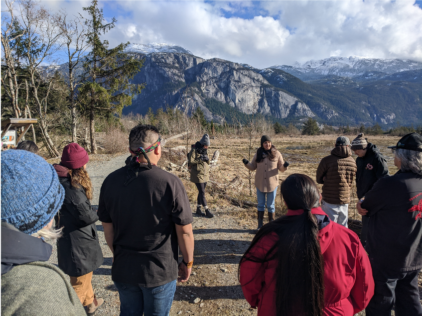 A group of people participate in a stewardship workshop in the Squamish estuary.